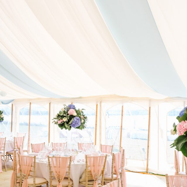 Pink chair sashes on chairs and flower arrangements in marquee