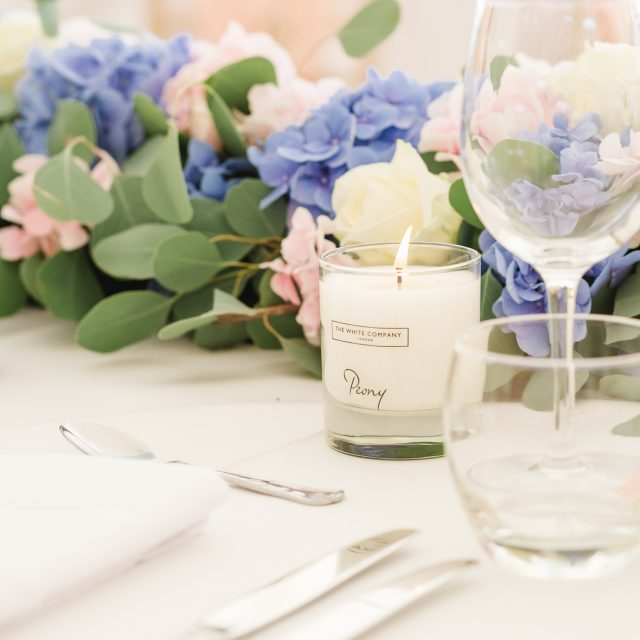blue and pink hydrangea table arrangement and candle