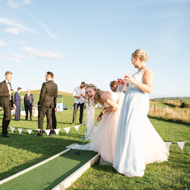 Bride playing mini golf at wedding at Porthilly Farm, Cornwall
