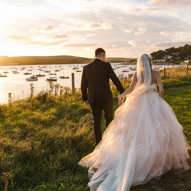 Bride and groom walking in field at Porthilly Farm in Cornwall