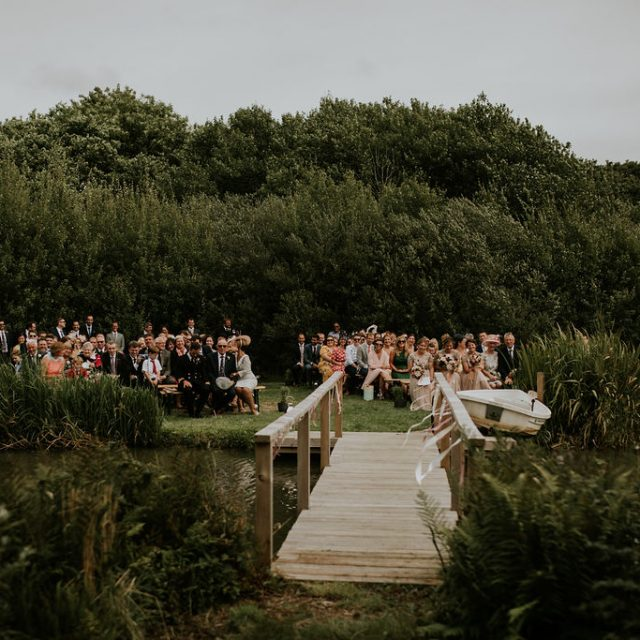 Guests seated for ceremony outside by kale at Trevibban Mill in Cornwall
