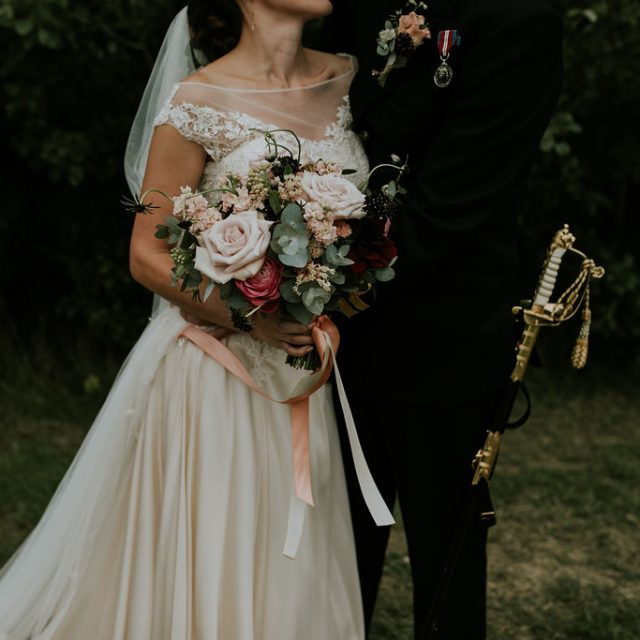 Brides blush pink bouquet and wedding dress, groom in navy uniform at wedding at Trevibban Mill in Cornwall