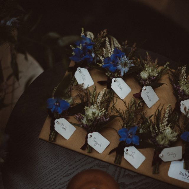 Cornflower blue buttonholes with name tags
