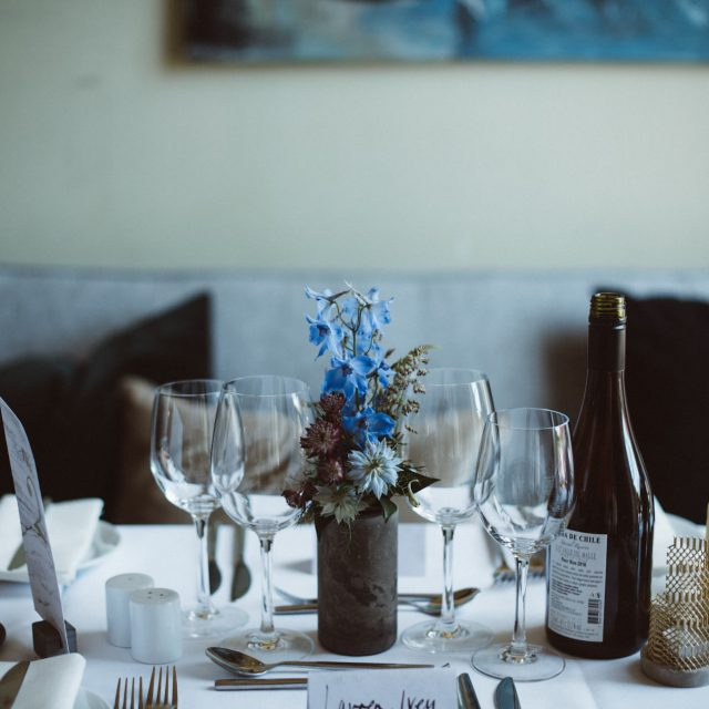 Cornflower blue wedding flowers on table with candles and glasses at Enys House, Cornwall