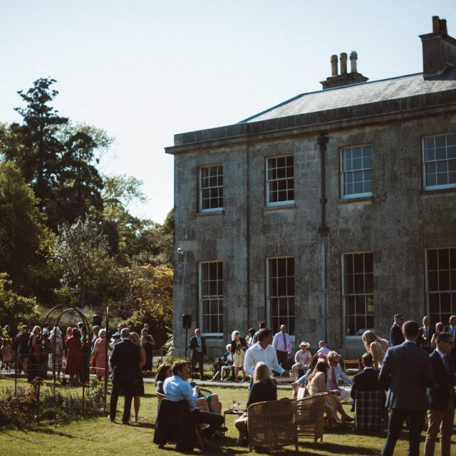 Guests having drinks on the lawns at a wedding at Enys House, Cornwall