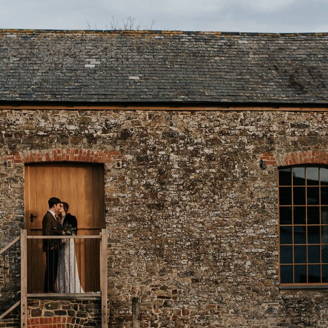 Bride and Groom outside the barn at styled wedding shoot at Launcells Barton, Cornwall