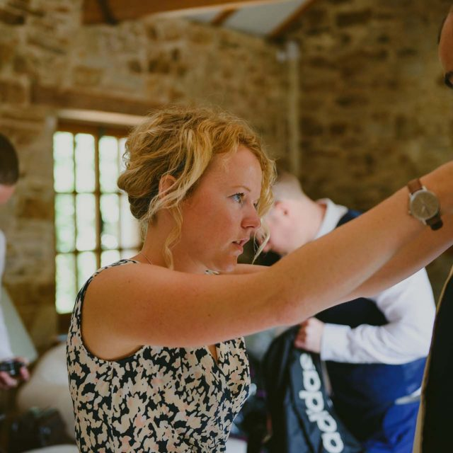 Jenny helping the groomsmen get ready at a private home wedding in Cornwall