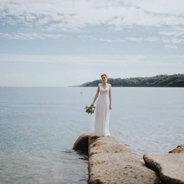 The bride by the water at a wedding at Trebah Gardens in Cornwall