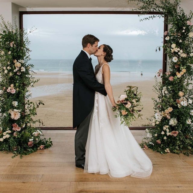 Tom and Rebecca enjoying their first photos as a married couple at the Watergate Bay Hotel in Cornwall